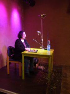 """Katja, lachend am gelben Lesetisch vor violetter Wand, in der """"Brelinger Mitte"""""""